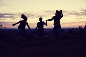 amici che saltano tedendosi per mano al tramonto