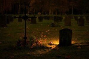 tomba illuminata al cimitero di notte